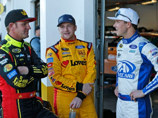 Clint Bowyer, left, Chris Buescher, center, and Trevor Bayne chat in the garage during practice for the NASCAR Daytona 500 auto race at Daytona International Speedway, Wednesday, Feb. 17, 2016, in Daytona Beach, Fla. (AP Photo/Wilfredo Lee)