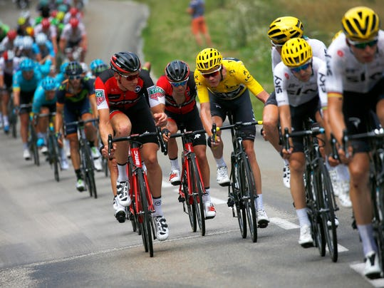 Britain's Chris Froome, wearing the overall leader's yellow jersey, talks to a team BMC rider during the eighth stage of the Tour de France cycling race over 187.5 kilometers (116.5 miles) with start in Dole and finish in Station des Rousses, France, Saturday, July 8, 2017. (AP Photo/Peter Dejong)