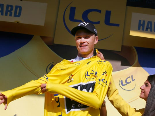 Britain's Chris Froome, puts on the overall leader's yellow jersey on the podium after the eighteenth stage of the Tour de France cycling race over 179.5 kilometers (111.5 miles) with start in Briancon and finish on Izoard pass, France, Thursday, July 20, 2017. (AP Photo/Peter Dejong)
