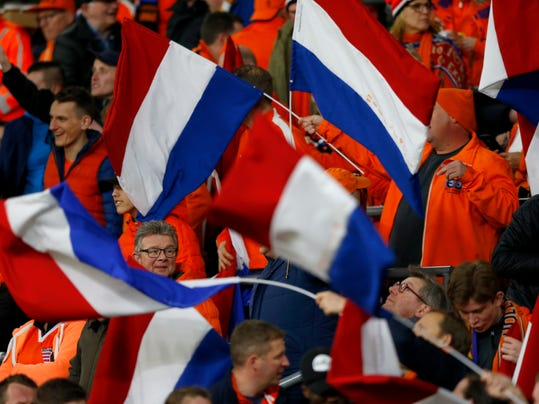 Dutch fans wave flags before the international friendly soccer match between the Netherlands and England at the Amsterdam ArenA in Amsterdam, Netherlands, Friday, March 23, 2018. (AP Photo/Peter Dejong)