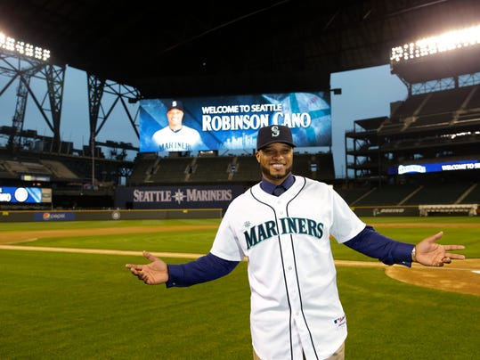 FILE - In this Dec. 12, 2013, file photo, Robinson Cano poses for a photo in his new jersey at Safeco Field in Seattle, after he was introduced as the newest member of the Seattle Mariners baseball team. Spring training is starting, and it's time for Robinson Cano, Shin-Soo Choo and a number of other big names to suit up for new teams. (AP Photo/Ted S. Warren, File)