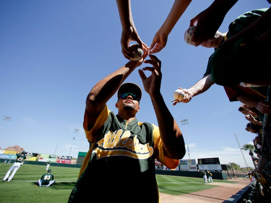 Oakland Athletics center fielder Coco Crisp signs autographs before a spring exhibition baseball game against the Seattle Mariners in Phoenix, Saturday, March 22, 2014. (AP Photo/Chris Carlson)