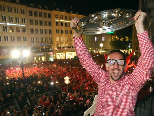 In this picture taken Saturday May 10, 2014,  Bayern Munich soccer player Franck Ribery , with funny glasses, raises the trophy  on the balcony of the city hall  during celebrations for Bayern's  Champions' title   in Munich , Germany.   (AP Photo/Alexander Hassenstein,Pool)