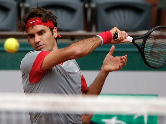 Switzerland's Roger Federer returns the ball during the third round match of the French Open tennis tournament against Russia's Dmitry Tursunov at the Roland Garros stadium, in Paris, France, Friday, May 30, 2014.  (AP Photo/Michel Euler)