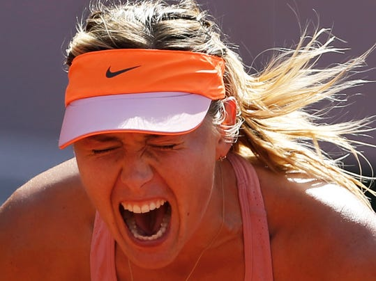 Russia's Maria Sharapova screams after scoring a point during final of the French Open tennis tournament against Romania's Simona Halep at the Roland Garros stadium, in Paris, France, Saturday, June 7, 2014. (AP Photo/Darko Vojinovic)