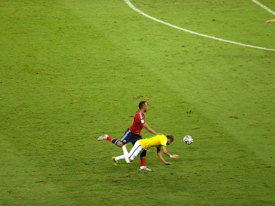 Brazil's Neymar, bottom, falls beside Colombia's Juan Zuniga during the World Cup quarterfinal soccer match between Brazil and Colombia at the Arena Castelao in Fortaleza, Brazil, Friday, July 4, 2014. (AP Photo/Themba Hadebe)