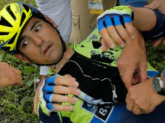Tinkoff Saxo team manager Bjarne Riis of Denmark and a Tour de France doctor help  Jesus Hernandez Blaquez of Spain after he crashed during the sixth stage of the Tour de France cycling race over 194 kilometers (120.5 miles) with start in Arras and finish in Reims, France, Thursday, July 10, 2014. Blaquez is a key climbing lieutenant for leader Alberto Contador of Spain had to abandon the race because of his injuries. (AP Photo/Christophe Ena)
