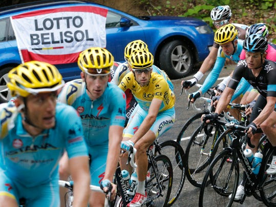 Team Astana with Italy's Vincenzo Nibali, wearing the overall leader's yellow jersey, passes a car with a banner of the Lotto Belisol team whose rider Tony Gallopin of France took over the yellow jersey during the ninth stage of the Tour de France cycling race over 170 kilometers (105.6 miles) with start in Gerardmer and finish in Mulhouse, France, Sunday, July 13, 2014. (AP Photo/Christophe Ena)