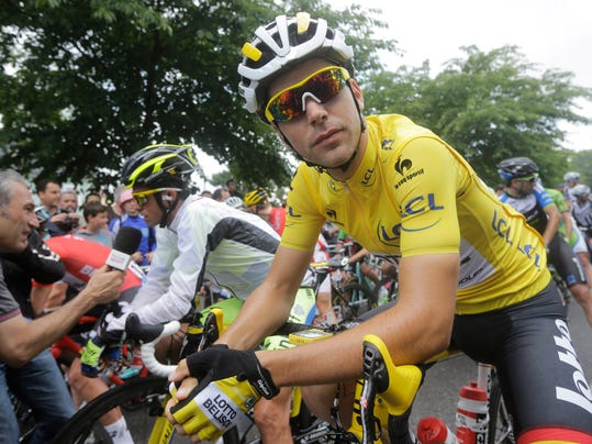 France's Tony Gallopin, wearing the overall leader's yellow jersey, waits for the start of the tenth stage of the Tour de France cycling race over 161.5 kilometers (100.4 miles) with start in Mulhouse and finish in La Planche des Belles Filles, France, Monday, July 14, 2014. Rear left is Spain's Alberto Contador who answers questions of reporters. (AP Photo/Laurent Cipriani)