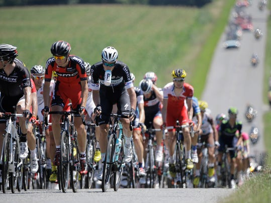 One rider holds a drinking bottle with his teeth as the rest of the pack blurs in the heat haze during the twelfth stage of the Tour de France cycling race over 185.5 kilometers (115.3 miles) with start in Bourg-en-Bresse and finish in Saint-Etienne, France, Thursday, July 17, 2014. (AP Photo/Laurent Cipriani)