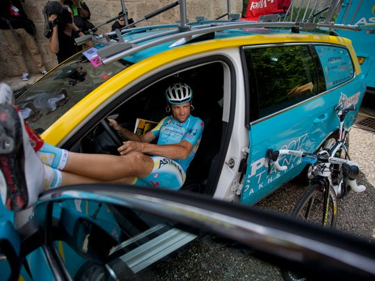 Italy's Michele Scarponi rests a little in a team car as he waits for the rest of the Astana team with overall leader Italy's Vincenzo Nibali, to go for a training on the second rest day of the Tour de France cycling race in Lignan-sur-Orb, southern France, Monday, July 21, 2014. (AP Photo/Peter Dejong)