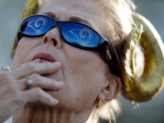 St. Louis Rams fan Lois Linton, of Collinsville, Ill., watches the Rams' first official workout of training camp at the NFL football team's practice facility on Friday, July 25, 2014, in St. Louis. (AP Photo/Jeff Roberson)