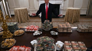 In this Jan. 14, 2019 photo, President Donald Trump talks to the media about the table full of fast food in the State Dining Room of the White House in Washington, for the reception for the Clemson Tigers. The partial government shutdown is hitting home for President Trump in a very personal way. He lives in government-run housing, after all.