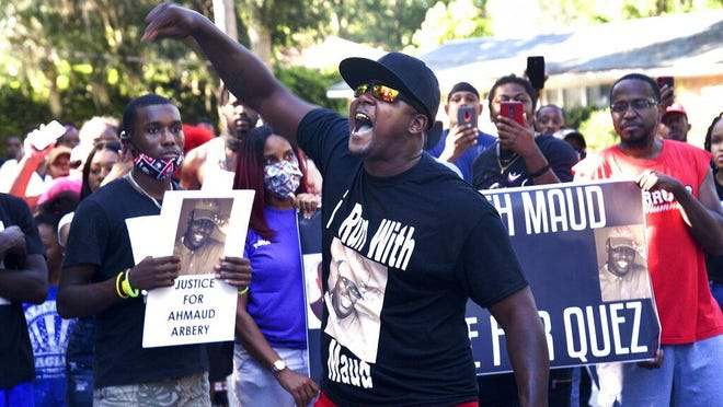 In this Tuesday, May 5, 2020, Keith Smith speak to a crowd as they march through a neighborhood in Brunswick, Ga. They were demanding answers in the death of Ahmoud Arbery. An outcry over the Feb. 23 shooting of Arbery has intensified after cellphone video that lawyers for Arbery's family say shows him being shot to death by two white men.