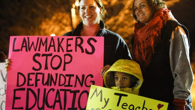 Melissa Fore, of East Lansing, and her daughter Lola, a first-grader at Marble Elementary, and East Lansing parent Heather Sprague gathered outside MacDonald Middle School in November in East Lansing to show their support for East Lansing teachers.