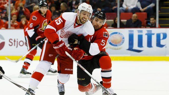 Oct 30, 2015; Detroit, MI, USA; Detroit Red Wings center Riley Sheahan (15) skates with the puck as Ottawa Senators defenseman Cody Ceci (5) defends in the first period at Joe Louis Arena.