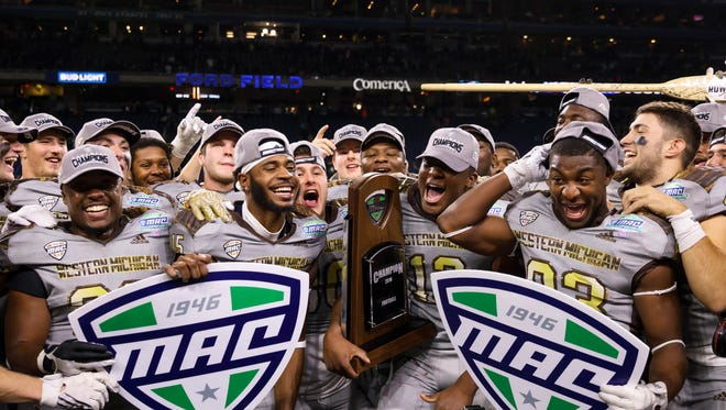 Western Michigan celebrates after defeating Ohio for the MAC Championship. The league will pocket money from the Broncos' College Football Playoff game.
