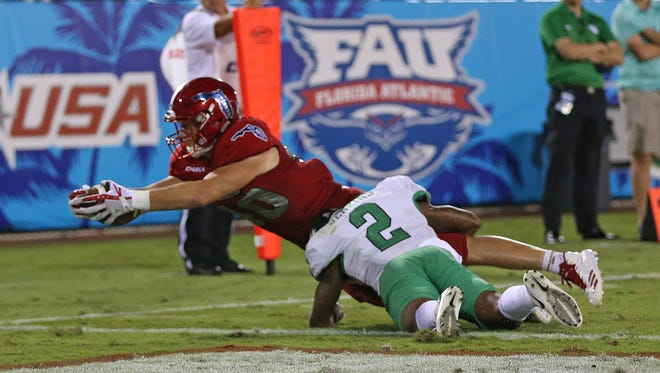 Florida Atlantic's Harrison Bryant leaps past North Texas defender Eric Jenkins for a touchdown during the Owls' 69-31 victory on Saturday.