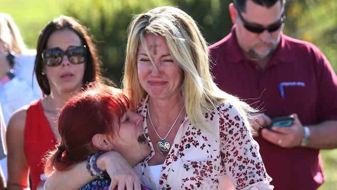 Parents wait for news after reports of a shooting at Marjory Stoneman Douglas High School in Parkland, Fla., on Wednesday, Feb. 14, 2018.