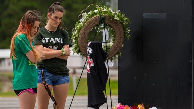 Kalysta Dodson, left, and Reagyn Murphy, sophomores at Santa Fe High School, look at a memorial for the victims of the Santa Fe High School.