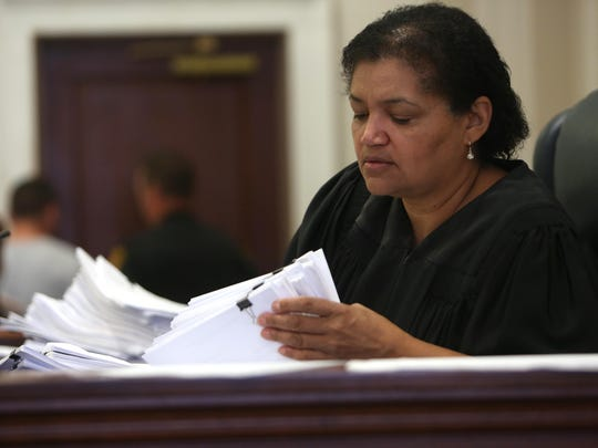 Hamilton County judge Kim Burke riffles through a stack of cases while overseeing her morning arraignments on May 21. Burke deals with non-violent offenders who are allowed to remain out of jail if they accept more stringent probation and promise to participate in treatment programs. At least once a week, her docket is packed with addicts in the program who have flunked drug tests.