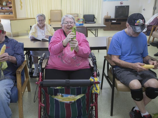 Billy Meyers, left, Jenny Davis and Randy Raney shuck corn July 30 during activity time at the Davis Center, a nursing home near Bloomfield that specializes in handling elderly people with mental illness.