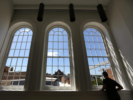 Eric Weissmann, director of marketing at Cintrifuse, looks through the windows of a conference room at the newly renovated Union Hall.