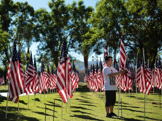 Allen Zhao, 16, a Chinese exchange student at Marywood Palm Valley helps put up flags for the Healing Field display on the corner of Dinah Shore and Date Palm Dr. in Cathedral City on Saturday, November 8, 2014. Over 100 volunteers posted  5100 flags to pay tribute to veterans.