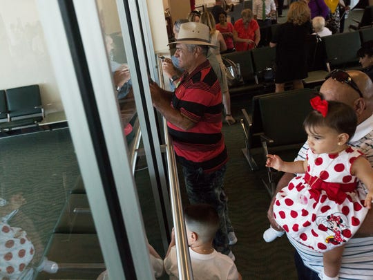 Raul Diaz, foreground, along with his grandchildren Jaylin Diaz, 10 mos, and Jayden Diaz, lower left, along with Vincente Antonio Rodriguez, center, watch as the first flight Choice Aire from Havana, Cuba arrives at Southwest Florida International Airport on Monday.  All were on return flight back to Cuba.  Rodriguez, who is from Lehigh Acres was going to visit family members.