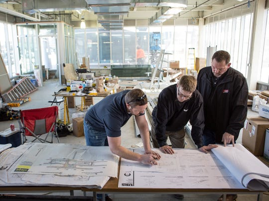 Contractors Jack Page, Trey Neubauer and Dave Murray looks over blueprints inside what will become a store operated by St. Clair County Community Mental Health Friday, Jan. 29, 2016 at the Blue Water Transit Bus Center in downtown Port Huron.