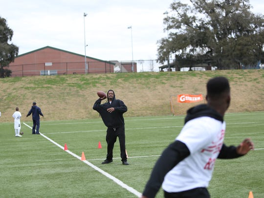 Pensacola's Michael Redding Jr. throws warm-up passes to his eighth grade son Michael Redding III during a Florida FSG 7-on-7 tryout on Saturday, Feb. 6.