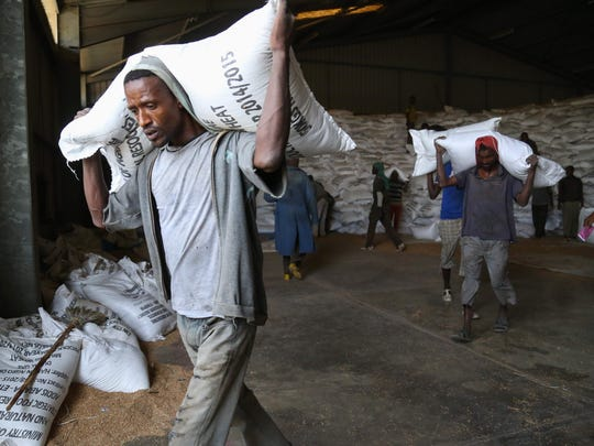 Workers move sacks of emergency food supplies in and out of Ethiopia's largest strategic grain reserve depot in Adama.