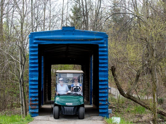 Sue Bannister, of Fort Gratiot, and Dawn Anglin-Spencer, of Port Huron, drive in a golf cart through a bridge over Cuttle Creek Thursday, May 12, 2016 at the Marysville Golf Course.