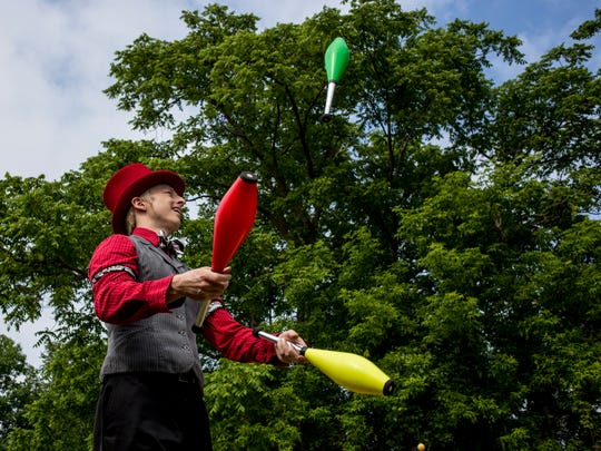 Performance artist Eric Scott Baker, of Detroit, juggles colorful pins at the entrance during the Croswell Fair Wednesday, June 15, 2016 at the fairgrounds in Croswell.
