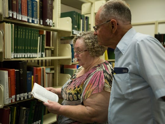 "President of the Doña Ana County Genealogical Society Georgie McDougle, left, and secretary Bruce Pearson look through the book ""Mesilla Valley Pioneers"" at Branigan Library."