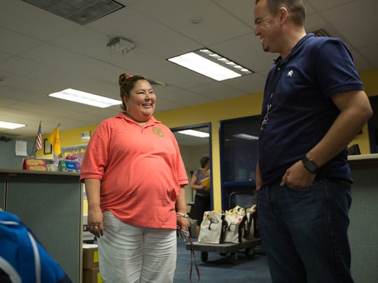 Southern New Mexico Correctional Facility Unit Director Nina Salcido-Marquez, left, delivers backpacks donated from inmates in the PAWS program, August 4, 2016, to MacArthur Elementary Principal Roberto Lozano. In all, prisoners and prison employees donated 24 backpacks with school supplies to three schools.
