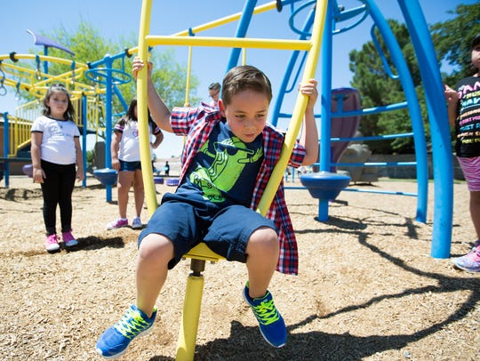 Second-grader Caleb Lujan, center, plays during recess,