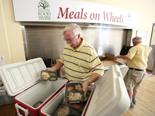 Gary Grombacher, left, who volunteers twice a week for Marion-Polk Food Share Meals on Wheels, picks up meals from Center 50+ prior to deliveries on Friday, Aug. 12, 2016, in Salem.