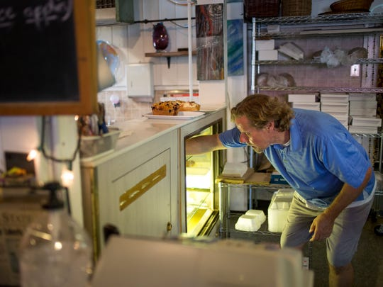 Roger Hages removes baked goods from a display case as they close Friday, August 19, 2016 at Diana's Bakery and Spun Gallery in Worth Township. The store will be closing for the season on Saturday. The M-25 bridge over Mill Creek will close Monday, Aug. 22, and is expected to reopen in November.