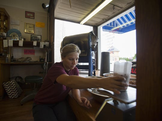 Aug. 25, 2016: Meeka Mohler weighs their own roasted peanuts at Michael's Ice Cream. The Appalachian Highway's namesake, former Ohio Gov. James A. Rhodes, once hand-cranked a peanut roaster for Mohler's great-grandfather when he ran the store.