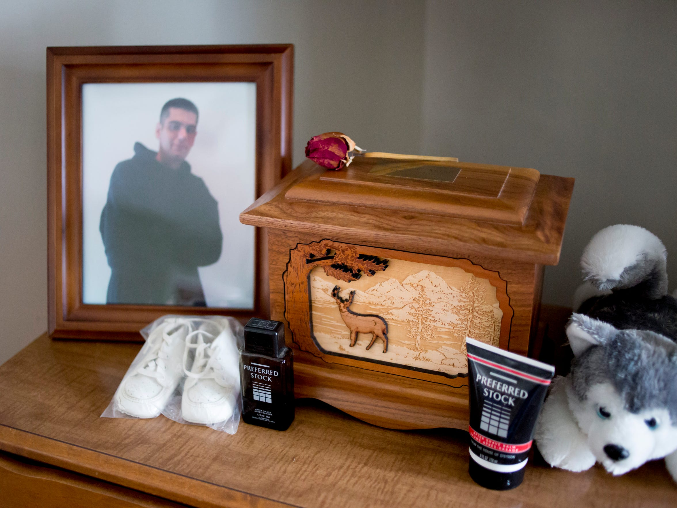An urn containing Bradley Moore's ashes sits on a dresser in his bedroom.