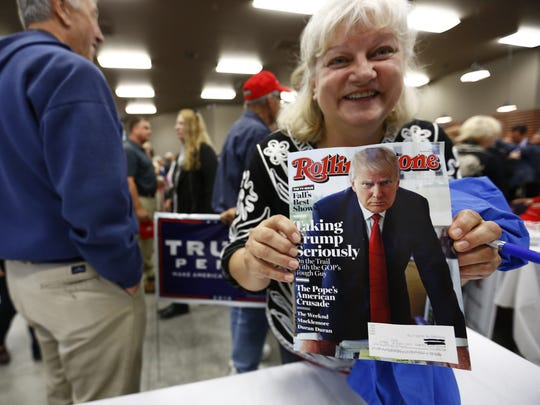 A woman shows off a Donald Trump magazine cover at a rally in the town of Marathon on Oct. 5. Donald Trump Jr. headlined the event at Zingers & Flingers, an indoor shooting range.