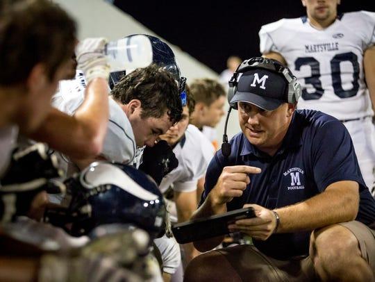 Marysville coach Mark Caza talks with players on the