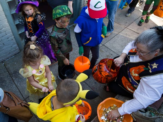 Leanna Hughes, owner of A Potpourri of Shops, hands out candy to kids trick or treating before the Ghostly Stroll parade in downtown Newburgh, In., on Saturday afternoon.