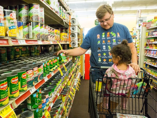 """Zach Eason shops with Luna, 2, on a recent Sunday. Zach says he often feels uncomfortable shopping with Luna because her skin color is darker than his. """"A lot of people look at me weird. They look at Luna and look back at me,"""" he said."""
