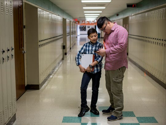 Jonas McCulloch, 12, talks with his translator, Ryan Zheng, as they look for his next class on his first day of school Thursday, Jan. 12, 2017 at Marine City Middle School.