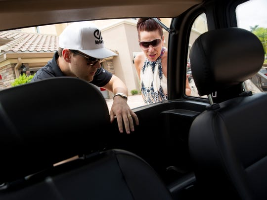 """Alex Maz, owner of MyCar EV, runs through the highlights of one of his golf cart models with potential customer Annemarie Drkulec, a seasonal resident from Windsor, Ontario, at her home Friday, July 7, 2017, at The Quarry in Naples. """"It's just to get around the community,"""" she said. """"What's not to like?"""""""