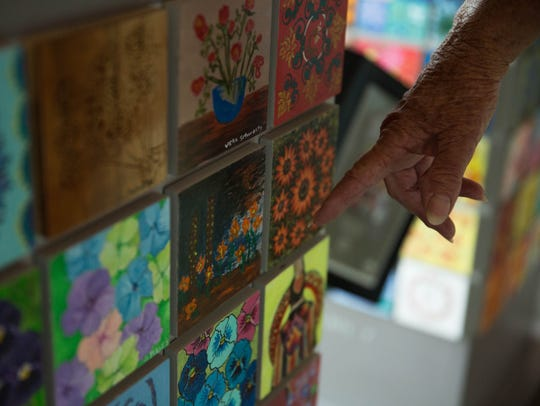 Ingeborg Peter's points to a tile she painted on the