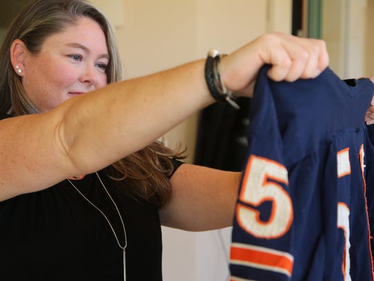 Samantha Buono holds up an old practice jersey which her father, former NFL player Mike Pyle, wore as a player for the Chicago Bears, October 3, 2017.
