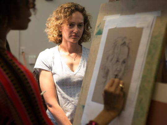 """An artist draws the face of her subject during  'Portraits of Wilmington"""" Sunday at the Delaware Museum of Art. The event gave 40 people the chance to sit in front of nearly a dozen artists to have their portrait made."""
